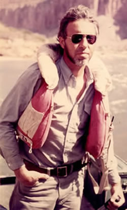 Gaylord Staveley in the early 1970s steering a Grand Canyon river raft and wearing an old PFD3